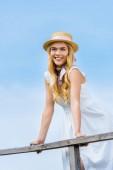 Fotografie krásná usměvavá blondýnka v proutěné klobouk v dřevěné zábradlí proti modré obloze