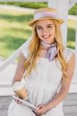 Fényképek szép mosolygó fiatal nő, kalap tartó kávé, hogy menjen és digitális tábla a parkban a padon ülve