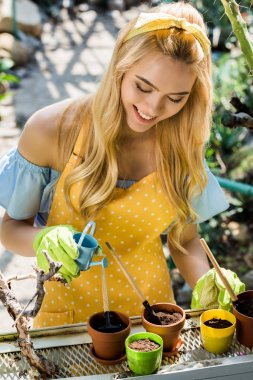 beautiful smiling young woman watering pots with small watering can