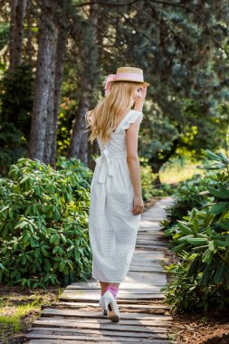 back view of beautiful girl in white dress and wicker hat walking on wooden walkway in park