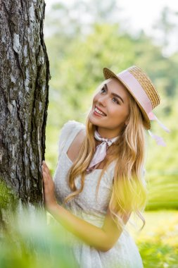 Selective focus of beautiful girl in dress and wicker hat leaning at tree and looking away stock vector