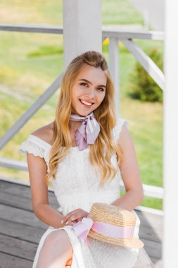 Beautiful blonde girl in white dress holding wicker hat while sitting on bench and smiling at camera stock vector