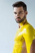 Uomo barbuto bello con il corpo coperto di liquido giallo isolato su priorità bassa bianca