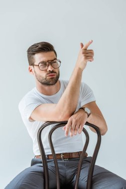 Handsome bearded man sitting on chair and pretending shooting isolated on white background