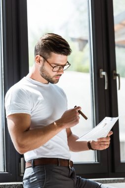 Handsome bearded businessman smoking cigar and reading document