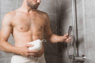 Handsome bearded man holding sponge behind shower glass