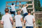 Rückansicht von multikulturellen Soldaten, die an Sommertagen Hindernislauf auf dem Schießstand üben