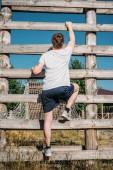 Rückansicht Soldat klettert bei Hindernislauf auf Schießanlage auf Holzbarriere