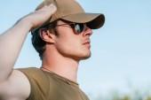 Fotografia vista laterale di giovane soldato in protezione ed occhiali da sole contro cielo blu