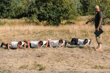 tactical instructor with notepad examining multicultural soldiers doing push ups on range