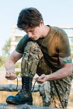portrait of soldier in military uniform tying shoelaces