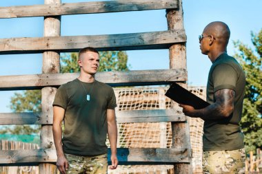 african american tactical instructor with notepad and young soldier in military uniform on range