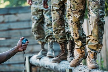 Partial view of tactical instructor with stop watch examining multiracial soldiers during obstacle run on range stock vector
