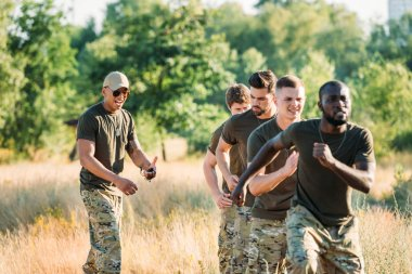 African american tactical instructor with stop watch examining multiracial soldiers during obstacle run on range stock vector