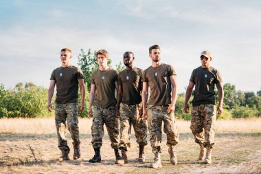 interracial soldiers in military uniform with tag dogs walking on range on summer day