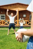 Fotografia bella giovane famiglia che gioca con la sfera di pallavolo sul giardino
