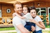 Fotografie mladá rodina zahrnující v zahradě dřevěnou chatku