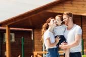 Fotografie schöne junge Familie umarmen vor Holzhaus