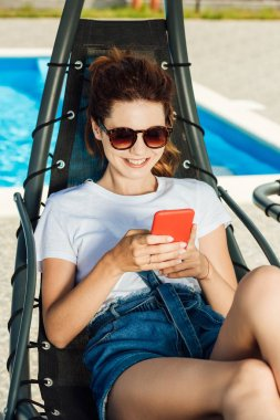 smiling young woman using smartphone while relaxing on sun lounger in front of swimming pool