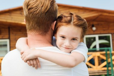 rear view of father embracing his adorable little daughter while she looking at camera