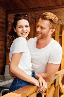 happy young cuddling couple in white t-shirts on terrace of wooden cottage