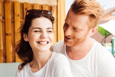 close-up portrait of young cuddling couple in white t-shirts