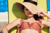 Fotografie close-up portrait of attractive young woman in straw hat and bikini relaxing on sun lounger at poolside