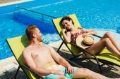 happy young couple flirting while relaxing on sun loungers in front of swimming pool