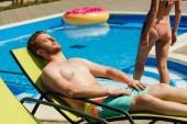 egy nyugágyon, miközben megy a medence barátnője barnító csinos, fiatal férfi