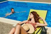 mladá žena na lehátku zatímco její přítel, plavání v bazénu na pozadí relaxační