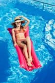 mosolygó fiatal nő Szalmakalapot és bikini úszó medence felfújható matrac