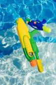 Fotografie plastové barevné vodní pistole plovoucí v bazénu