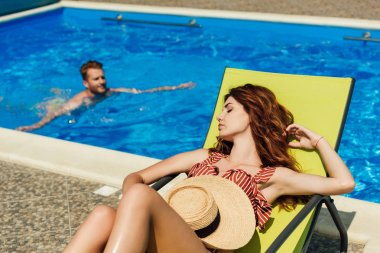 young woman relaxing on sun lounger while her boyfriend swimming in pool on background