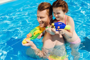 handsome father and adorable daughter playing with water guns in swimming pool