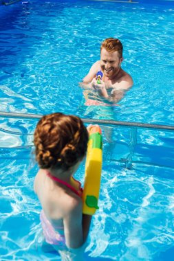 father and little daughter playing with water guns in swimming pool
