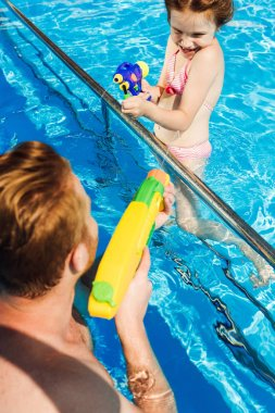 happy father and daughter playing with water guns in swimming pool