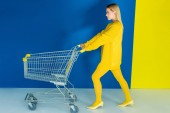 Fotografie Elegant blonde woman pushing shopping cart on blue and yellow background