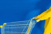 Cropped view of female hand on shopping cart on blue background