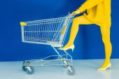 Photo Cropped view of woman leaning on shopping cart on blue background
