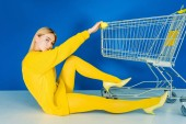 Fényképek Attractive young girl dressed in yellow sitting by shopping cart on blue background