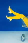 Photo Cropped view of female legs in shopping cart on blue background