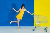 Modello di moda femminile che spinge il carrello su fondo blu e giallo