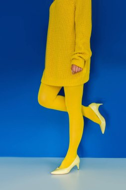 Cropped view of girl in yellow clothes and heeled shoes on blue background