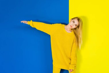 Attractive young girl posing in yellow clothes on blue and yellow background