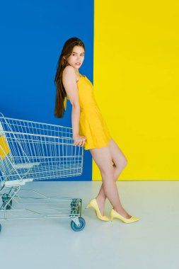 Fashion portrait of woman in yellow clothes leaning on shopping cart isolated on blue and yellow background