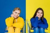 Fényképek Attractive young girls having fun sitting in shopping carts isolated on blue and yellow background