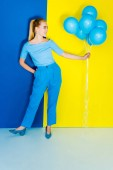 Fotografie Pretty blonde woman holding bunch of blue balloons on blue and yellow background