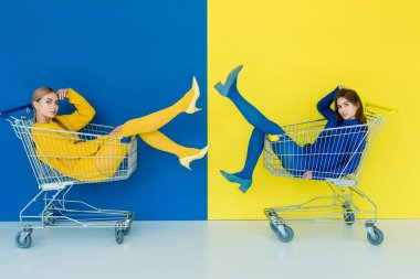 Beautiful brunette and blonde girls riding in shopping carts on blue and yellow background