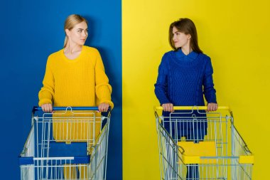 Smiling young women with shopping carts looking at each other on blue and yellow background
