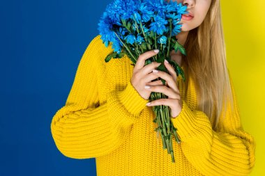 Girl in yellow sweater holding blue flowers isolated on blue and yellow background